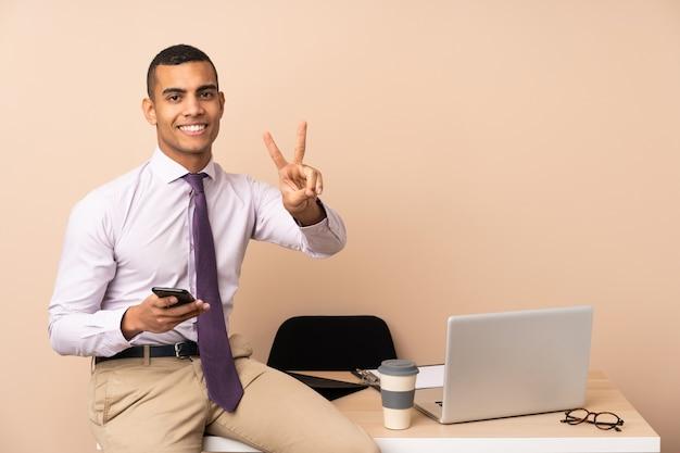 Jonge bedrijfsmens in een bureau dat en overwinningsteken glimlacht toont