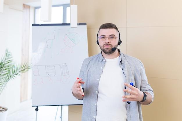Jonge bedrijfsmens in vrijetijdskleding die een hoofdtelefoon online vergaderingspresentatie draagt