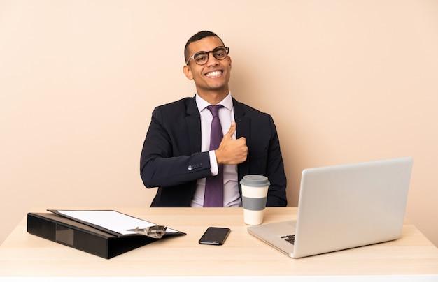 Jonge bedrijfsmens in zijn bureau met laptop en andere documenten die duimen op gebaar geven