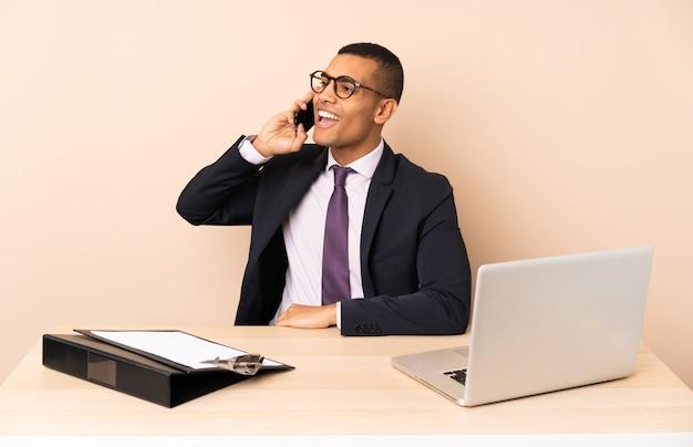 Jonge bedrijfsmens in zijn bureau met laptop en andere documenten die een gesprek met de mobiele telefoon houden
