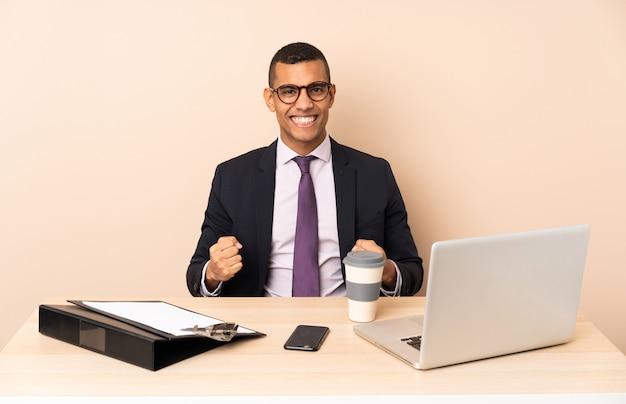 Jonge bedrijfsmens in zijn bureau met laptop en andere documenten die een overwinning in winnaarpositie vieren
