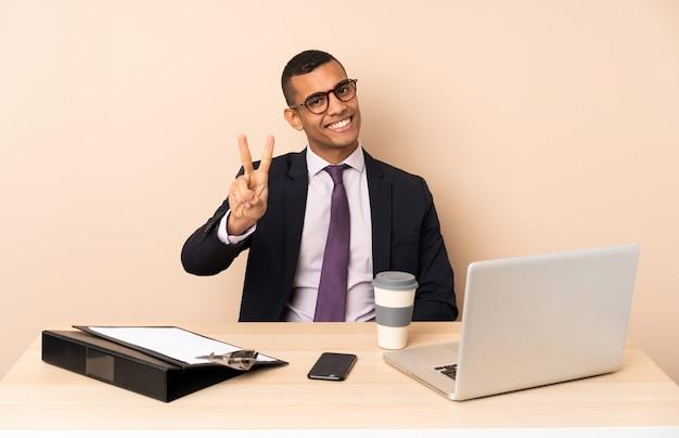 Jonge bedrijfsmens in zijn bureau met laptop en andere documenten die en overwinningsteken glimlachen tonen