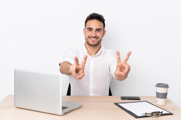 Jonge bedrijfsmens met een mobiele telefoon op een werkplaats die en overwinningsteken glimlacht toont