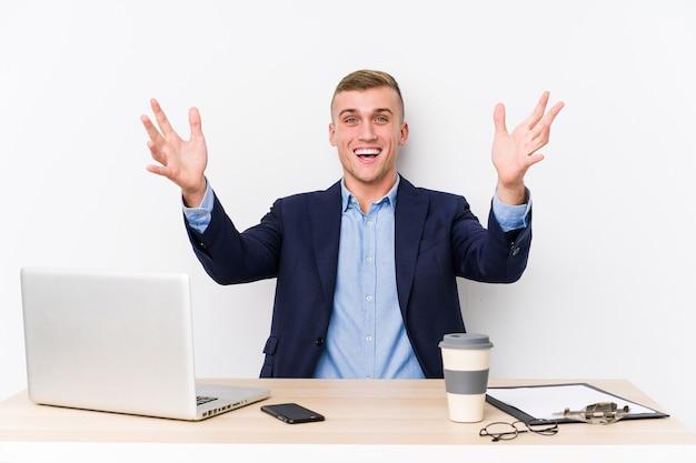 Jonge bedrijfsmens met laptop die een prettige opgewekte verrassing ontvangt en handen opheft.