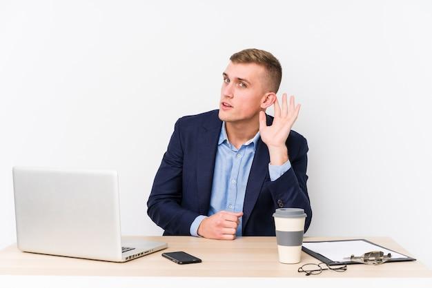 Jonge bedrijfsmens met laptop die een roddel proberen te luisteren.