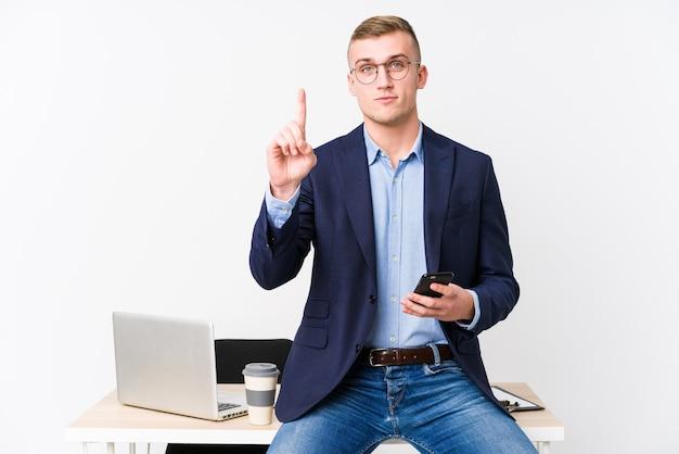Jonge bedrijfsmens met laptop die nummer één met vinger tonen.