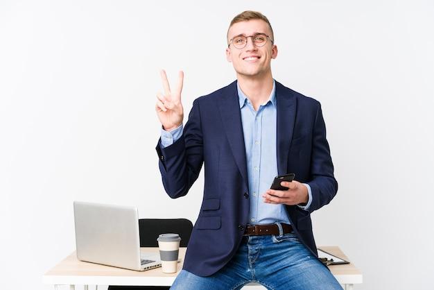 Jonge bedrijfsmens met laptop die nummer twee met vingers toont.