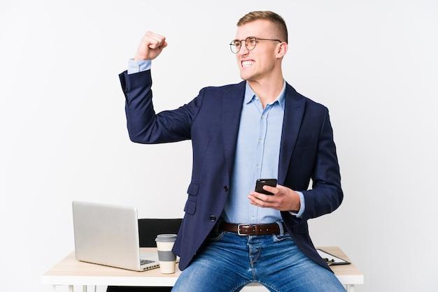 Jonge bedrijfsmens met laptop die vuist na een overwinning opheffen, winnaarconcept.