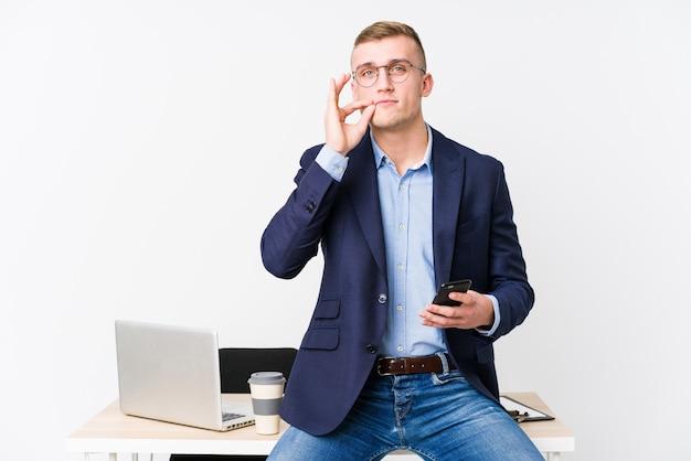 Jonge bedrijfsmens met laptop met vingers op lippen die een geheim houden.