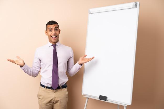 Jonge bedrijfsmens over geïsoleerde muur die een presentatie op wit bord en met geschokte uitdrukking geeft