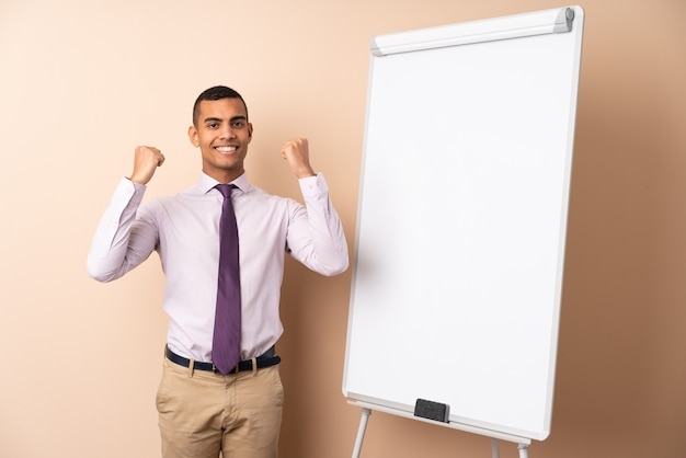 Jonge bedrijfsmens over geïsoleerde muur die een presentatie op wit bord geeft en een overwinning viert
