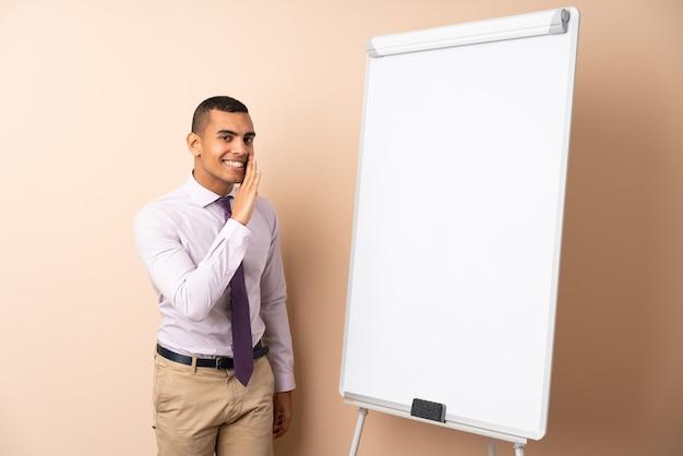 Jonge bedrijfsmens over geïsoleerde muur die een presentatie op wit raad geeft en iets fluistert