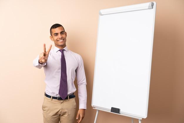 Jonge bedrijfsmens over geïsoleerde muur die een presentatie op wit raad geeft en overwinningsteken toont