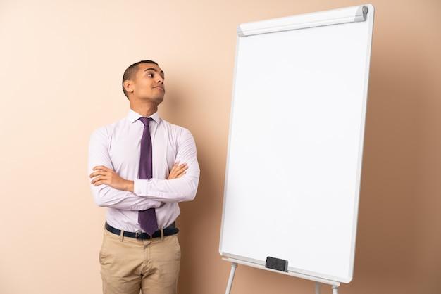 Jonge bedrijfsmens over geïsoleerde muur die een presentatie op wit raad geeft en twijfelsgebaar maakt