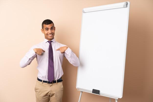 Jonge bedrijfsmens over geïsoleerde muur die een presentatie op witte raad en met verrassingsuitdrukking geeft