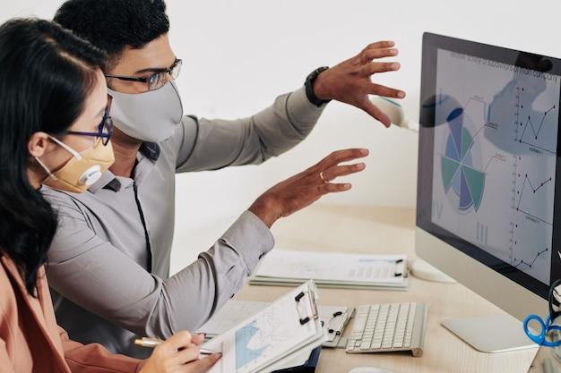 Jonge bedrijfsmensen die aan bureau zitten en grafieken en diagrammen op computerscherm bespreken
