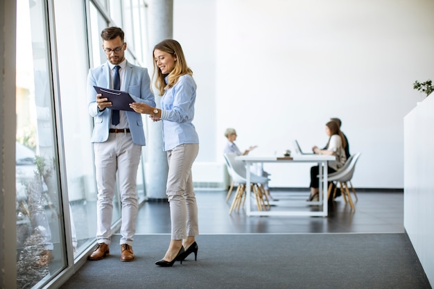 Jonge bedrijfsmensen die een dossier in een modern bureau zoeken