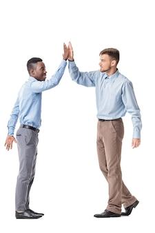 Jonge bedrijfsmensen die elkaar hoge vijf geven die op wit worden geïsoleerd