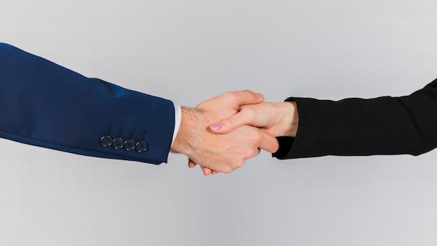 Jonge bedrijfsmensen die elkaars hand op een grijze achtergrond schudden