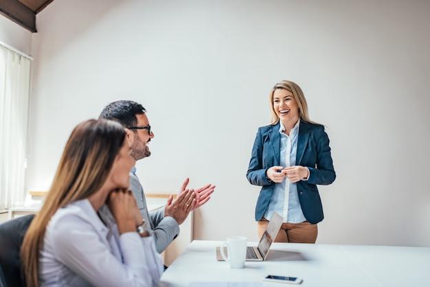 Jonge bedrijfsmensen die en na presentatie in de bestuurskamer slaan glimlachen.