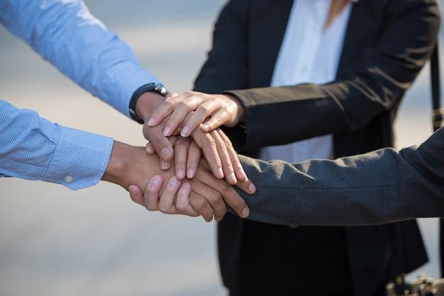 Jonge bedrijfsmensen die en zich samen bij hun handen in stapel zetten verenigen.