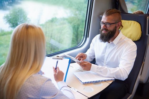 Jonge bedrijfsmensen die in de trein werken