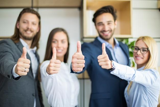 Jonge bedrijfsmensen met duim die omhoog in het bureau bevinden zich