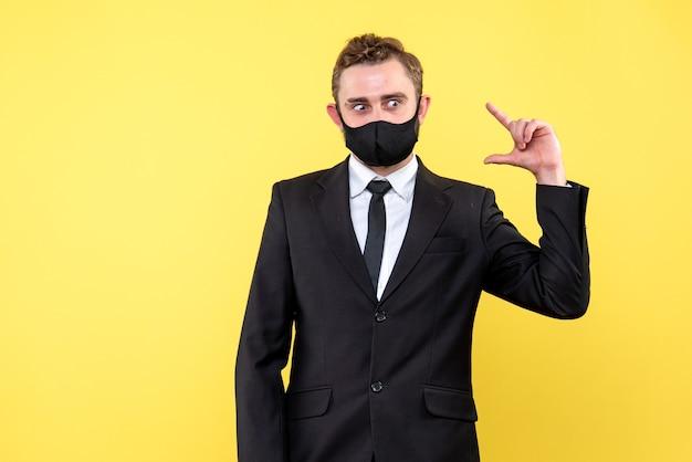 Jonge bedrijfspersoon die manier van oplossing met gezichtsmasker op geel uitdrukt