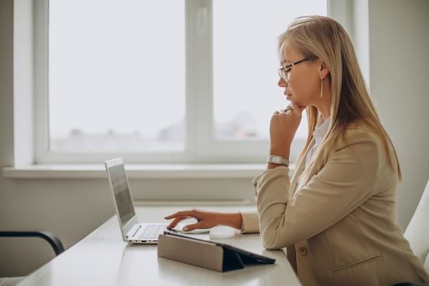 Jonge bedrijfsvrouw die aan computer in bureau werkt