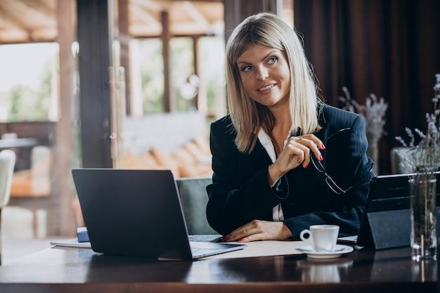 Jonge bedrijfsvrouw die aan computer in een koffie werkt
