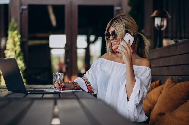 Jonge bedrijfsvrouw die aan computer in staaf werkt