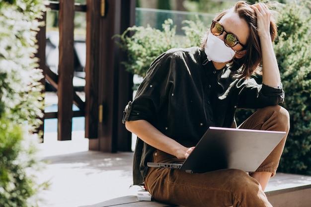 Jonge bedrijfsvrouw die aan computer van huis in masker werkt