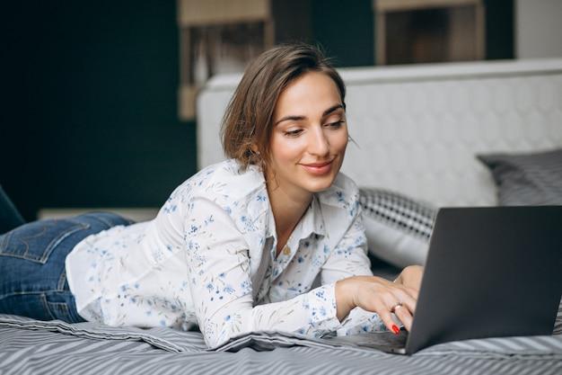 Jonge bedrijfsvrouw die aan een computer thuis werkt