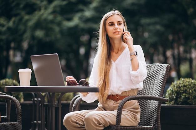 Jonge bedrijfsvrouw die aan laptop buiten in een koffie werkt