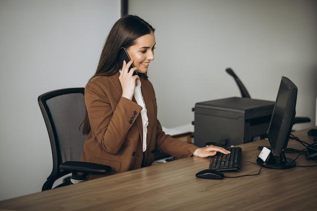 Jonge bedrijfsvrouw die aan laptop in bureau werkt