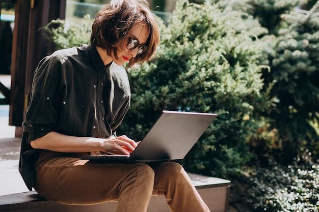 Jonge bedrijfsvrouw die aan laptop van huis werkt