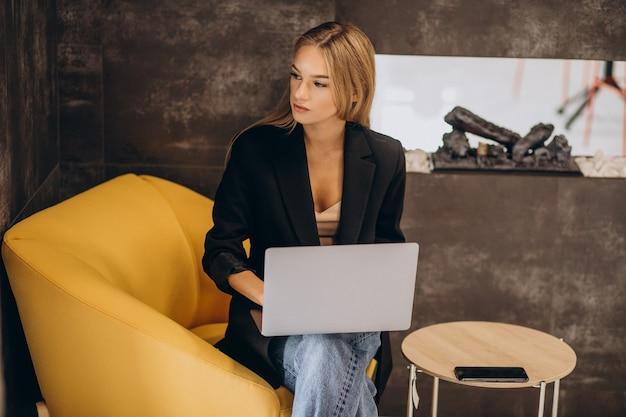 Jonge bedrijfsvrouw die aan laptop werkt
