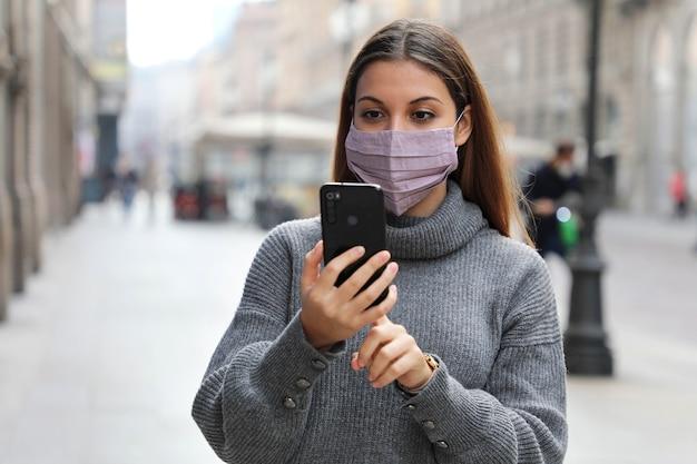 Jonge bedrijfsvrouw die bericht op mobiele telefoon in stadsstraat verzendt die gezichtsmaskerbescherming draagt