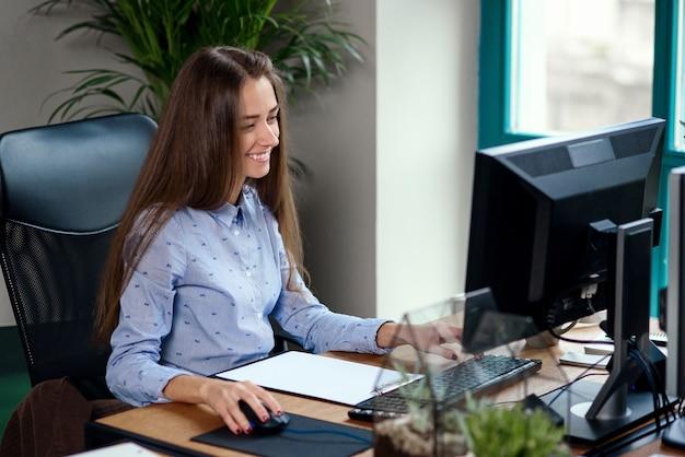 Jonge bedrijfsvrouw die bij computer in modern bureau werkt.