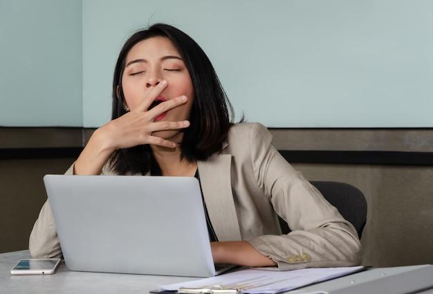 Jonge bedrijfsvrouw die bij het vergaderen van bureaulijst voor laptop geeuwt, die haar mond behandelen uit hoffelijkheid. overwerk en slaapgebrek concept