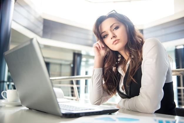 Jonge bedrijfsvrouw die bij laptop werkt.