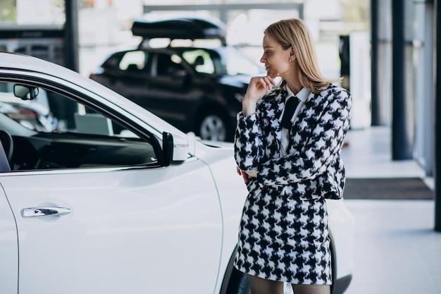 Jonge bedrijfsvrouw die een auto kiest