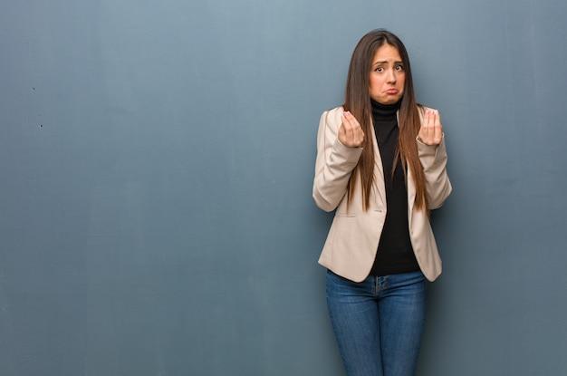 Jonge bedrijfsvrouw die een gebaar van behoefte doet