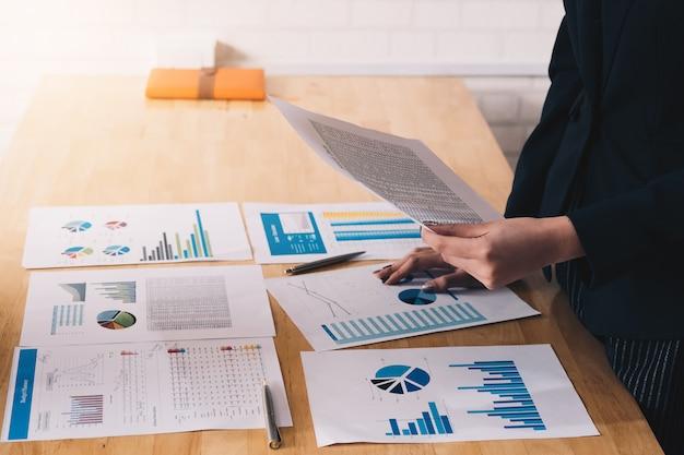 Jonge bedrijfsvrouw die een grafiek en een vennootschap houdt om het marketing plan te analyseren