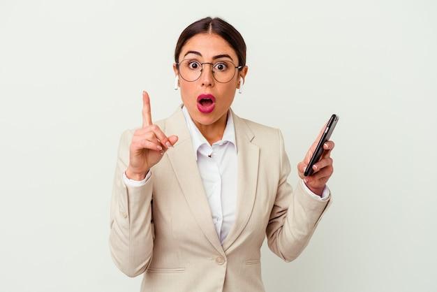 Jonge bedrijfsvrouw die een mobiele telefoon houden die op witte muur wordt geïsoleerd die een idee, inspiratieconcept heeft.