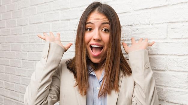 Jonge bedrijfsvrouw die een overwinning of een succes viert