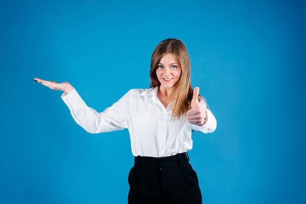 Jonge bedrijfsvrouw die en aan de camera glimlacht kijkt die met uw advertentie uw advertentie toont die over een blauwe achtergrond wordt geïsoleerd