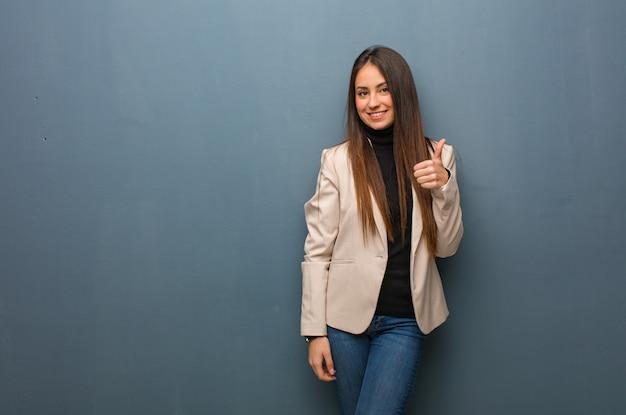 Jonge bedrijfsvrouw die en duim omhoog glimlacht opheft
