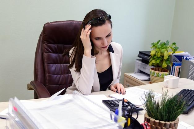 Jonge bedrijfsvrouw die hard over het bureau in de studie, de financiële rapportage van de econoomaccountant werken
