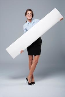 Jonge bedrijfsvrouw die het lege aanplakbord houdt
